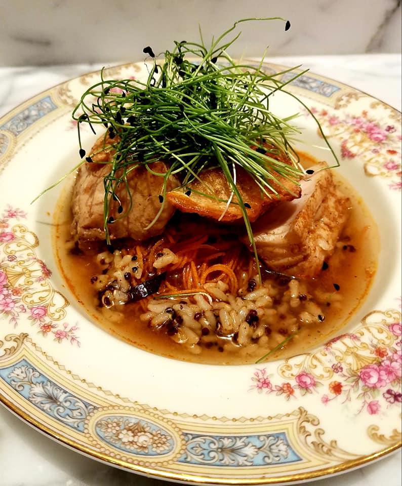Lemon grass poached gulf redfish accompanied by Louisiana crawfish potsticker set in opal basil seafood broth.